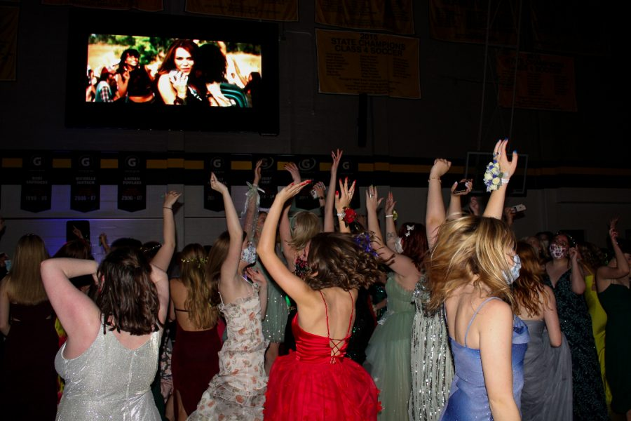 A group of seniors jump in the air and raise their arms while dancing at prom Apr. 16. This was the first and only STA prom held in the gym. photo by Caroline Hinkebein