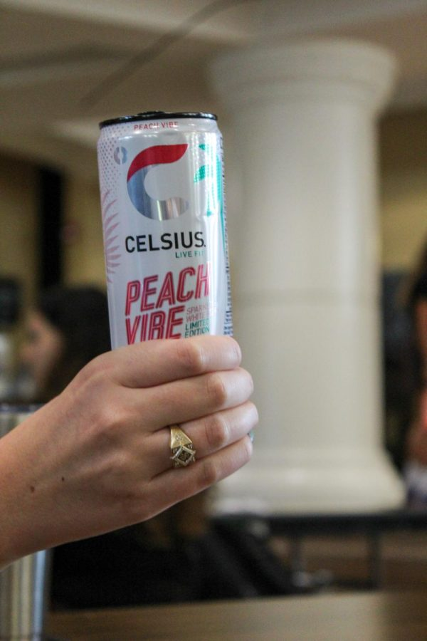 Senior Nina Burke holds a Celsius Sept. 7. This drink, though very popular, is controversial due to the abundance of unknown ingredients. photo by Katie Massman
