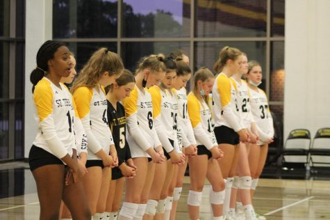 The varsity volleyball team bows their heads in prayer before their match against Blue Springs. There is a prayer for sportsmanship before every volleyball game.
